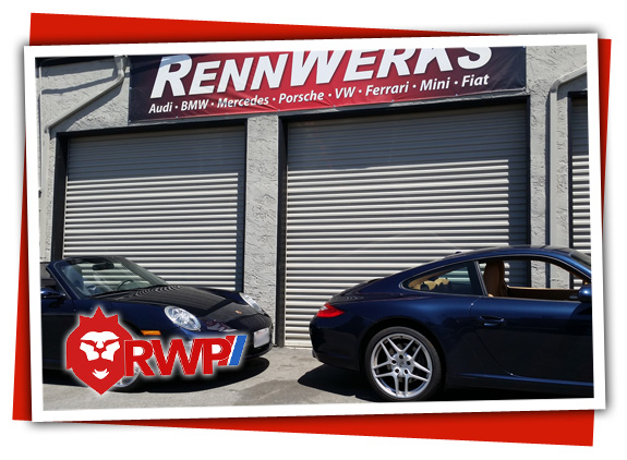 A pair of blue sister Porsche 997 cars in front RennWerks Garages